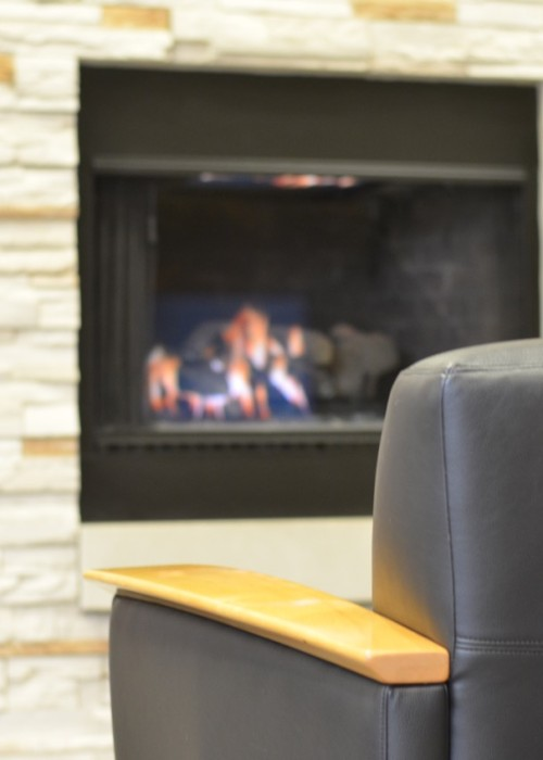 Cafe hours at Tamarac - Picture of a Chair in front of a lit fireplace.